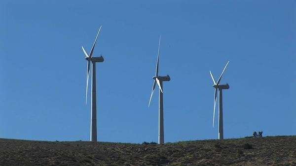 Long-shot of three wind turbines generating power at Tehachapi, California. Royalty-free stock video