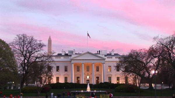 Medium shot of people walking by the White House at golden hour. Royalty-free stock video
