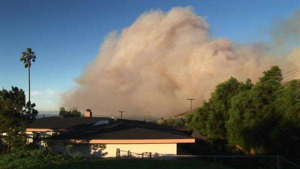 Long shot of a wall of smoke rising from wild fires around a Southern California community. Royalty-free stock video