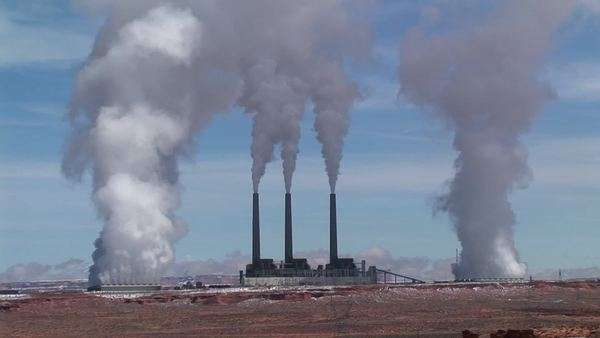 Medium-shot of a factory in the Arizona desert, belching polluting fumes into the air. Royalty-free stock video