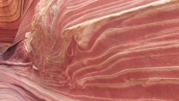 Pan-left of the layers of orange sandstone on a desert canyon wall. Royalty-free stock video