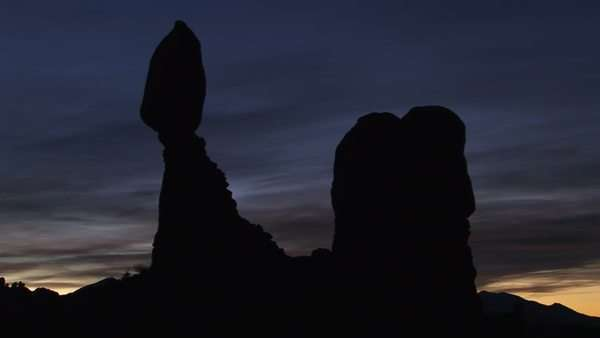 Balanced Rock is silhouetted against a dark sky in Arches National Park, Utah. Royalty-free stock video
