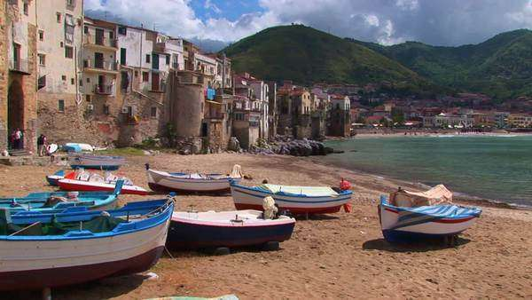 Boats sit on the sand near a coastal community. Royalty-free stock video