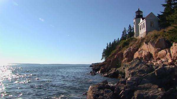 A lighthouse on the edge of a cliff overlooks the sparkling ocean. Royalty-free stock video