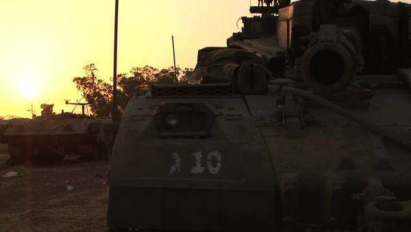 An Israeli tank is silhouetted against a multi colored sky. Royalty-free stock video