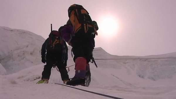 The sun beats down on climbers as they ascend icy slope Royalty-free stock video