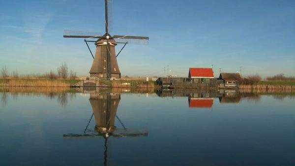 A windmill stands proudly along a canal in Holland. Royalty-free stock video