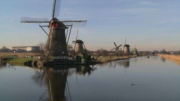 A boat moves along a canal in Holland with windmills nearby. Royalty-free stock video