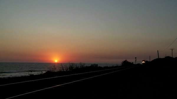 Beautiful shot of an Amtrak train passing by a California beach at sunset. Royalty-free stock video