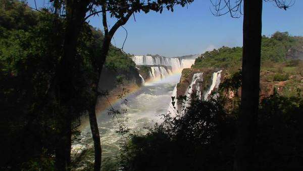 A wide shot of Iguacu Falls with a rainbow in the foreground. Royalty-free stock video