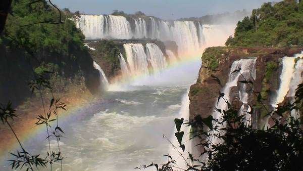 A zoom into Iguacu Falls with a rainbow in the foreground. Royalty-free stock video