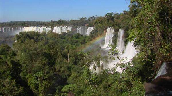 Iguacu Falls flows out of the jungle with a rainbow foreground. Royalty-free stock video