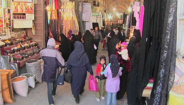Women wearing headscarfs and chadors pass through a bazaar in Iran. Royalty-free stock video