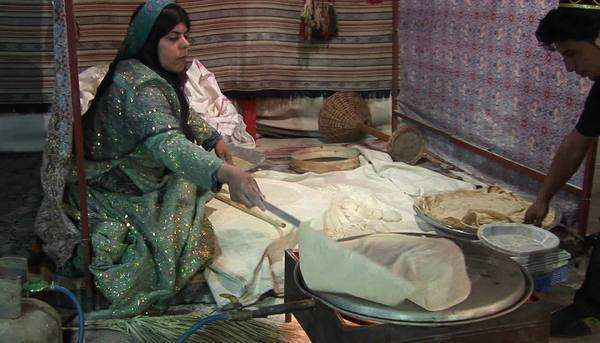 A woman wearing a headscarf bakes lavash bread on a tandori oven. Lavash is a traditional flatbread. Royalty-free stock video