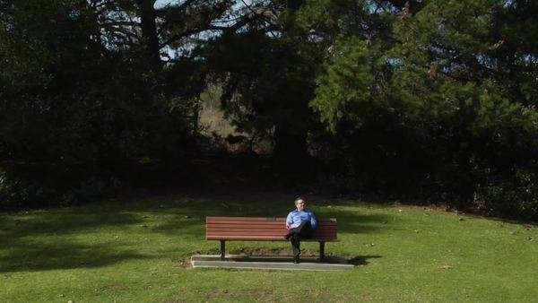 A man sits on a park bench alone with a flower. Royalty-free stock video
