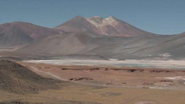 A truck passes through the colorful altiplano scenery surrounding the Salar de Laco in the altiplano high above San Pedro de Atacama Chile. Royalty-free stock video