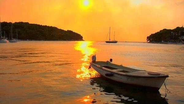 A small boat gently floats as a Croatian sunset transpires. Royalty-free stock video