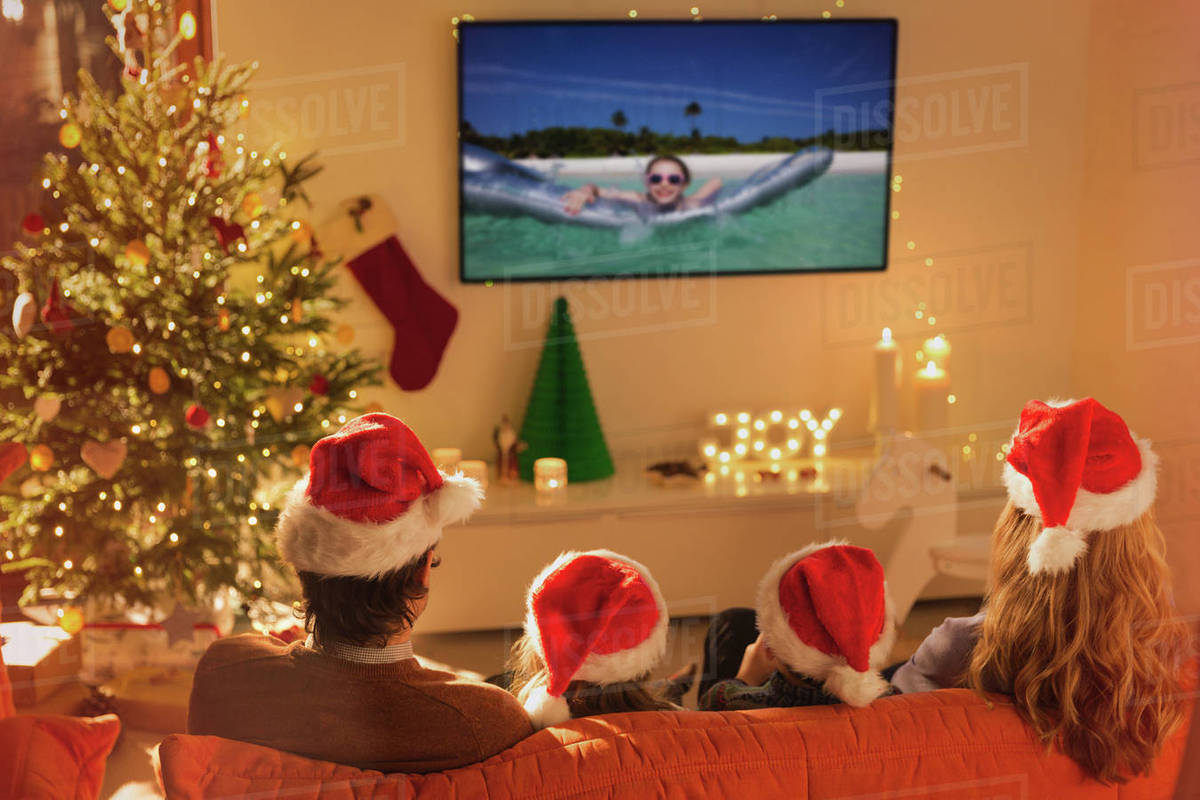 Family In Santa Hats Watching Summer Holiday Video On Tv In