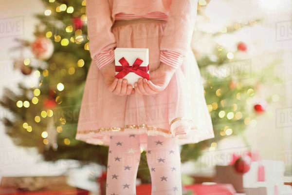 Girl in pink dress holding Christmas gift behind back in front of Christmas tree Royalty-free stock photo