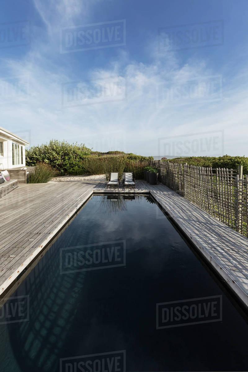 Dark luxury swimming pool under sunny blue sky D1007_10_328