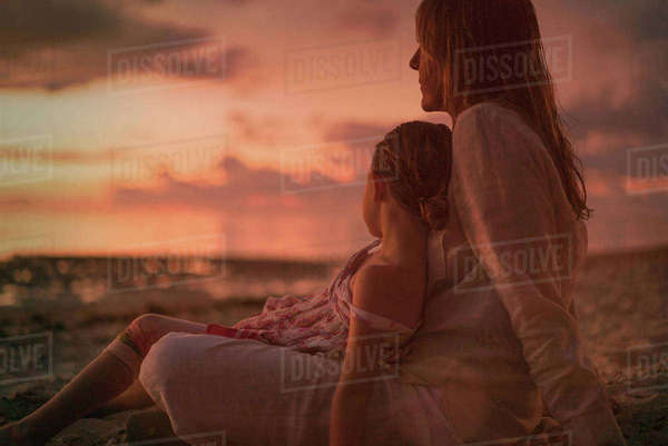 Serene mother and daughter relaxing on beach at dusk Royalty-free stock photo