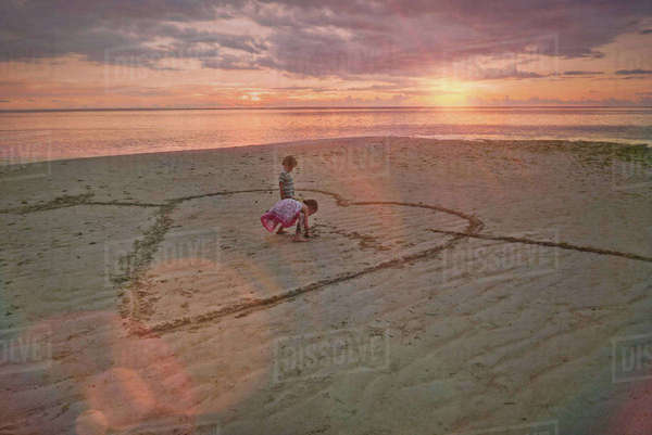 Boy and girl brother and sister drawing heart-shape in sand on tranquil sunset beach Royalty-free stock photo