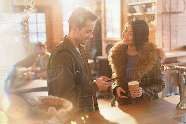 Couple with cell phone and coffee at counter in cafe Royalty-free stock photo