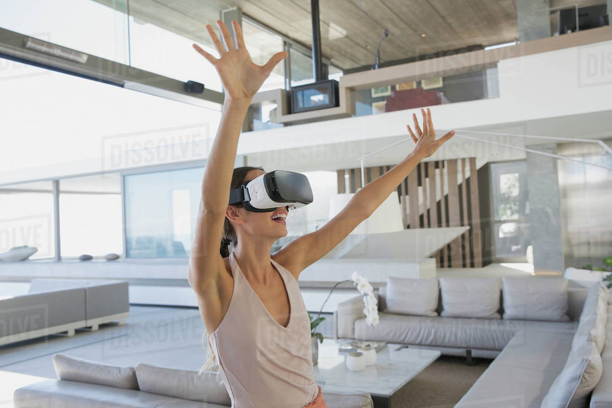 06a2eb13fc38 Energetic woman using virtual reality simulator glasses with arms raised in  modern