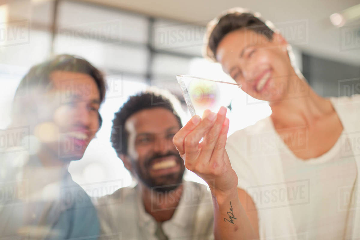 Smiling, curious, innovative entrepreneurs examining glass triangle  prototype stock photo