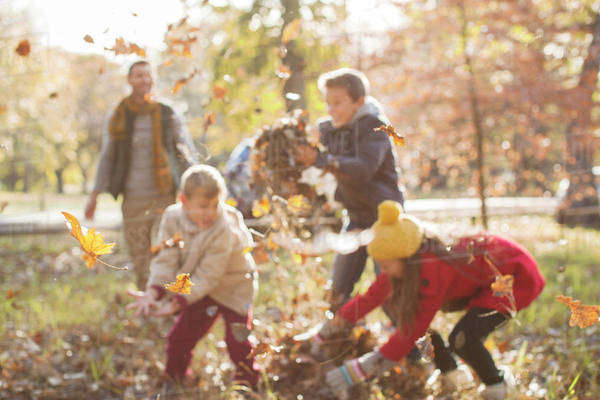 Family playing in autumn leaves at park Royalty-free stock photo
