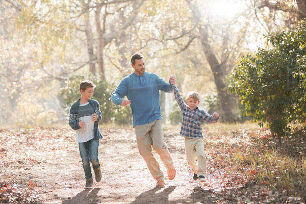Playful father and sons running on trail in woods Royalty-free stock photo