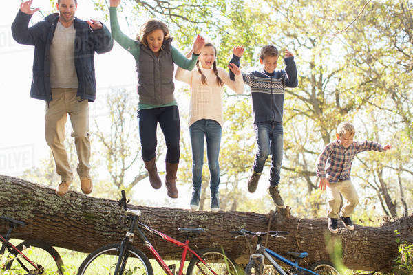 Enthusiastic family jumping from fallen log over bicycles Royalty-free stock photo