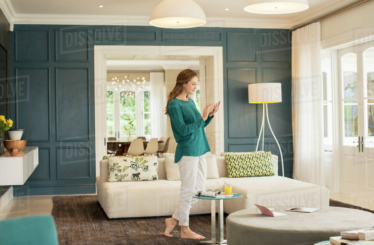 Woman texting with cell phone in home showcase living room Royalty-free stock photo
