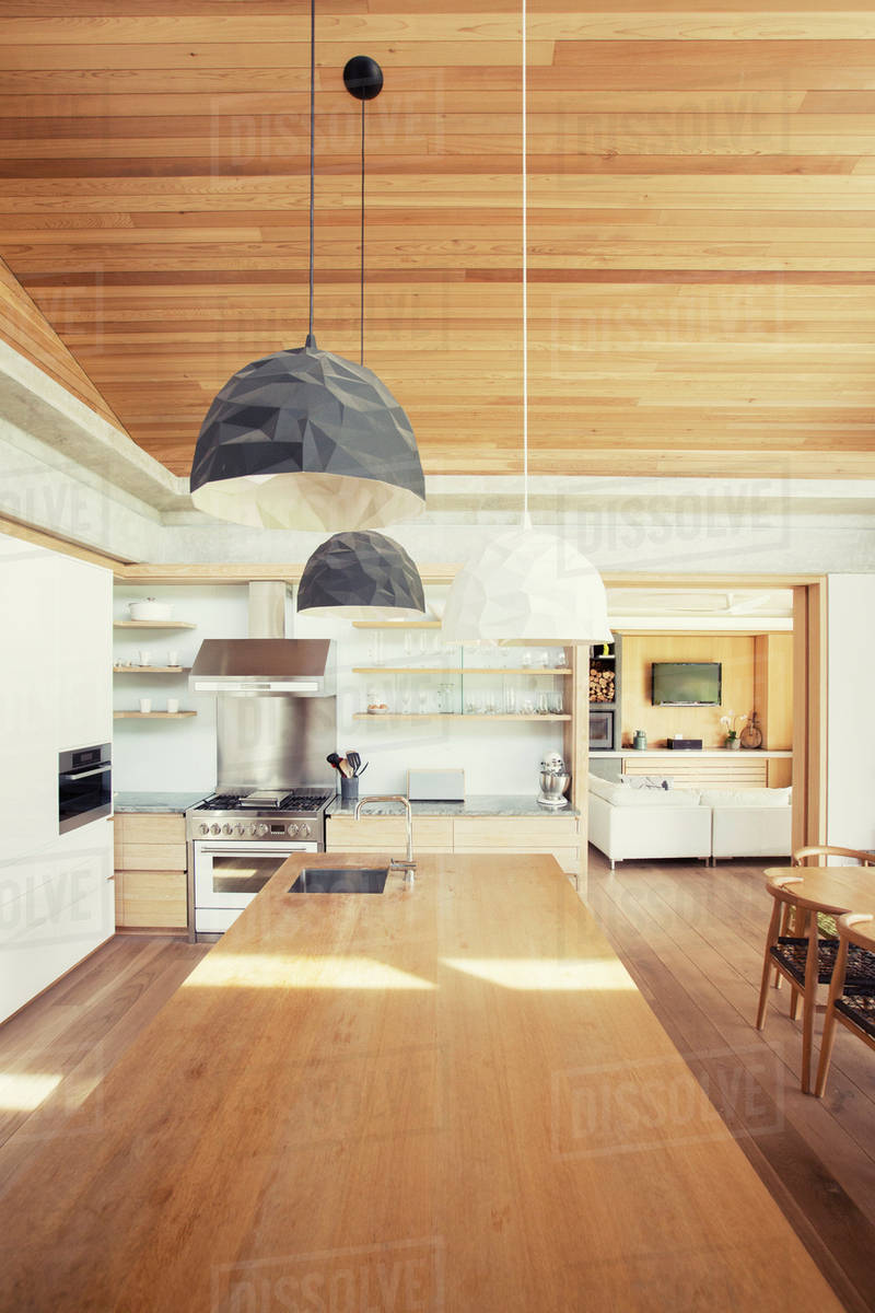 Modern pendant lights over long wood kitchen island stock photo