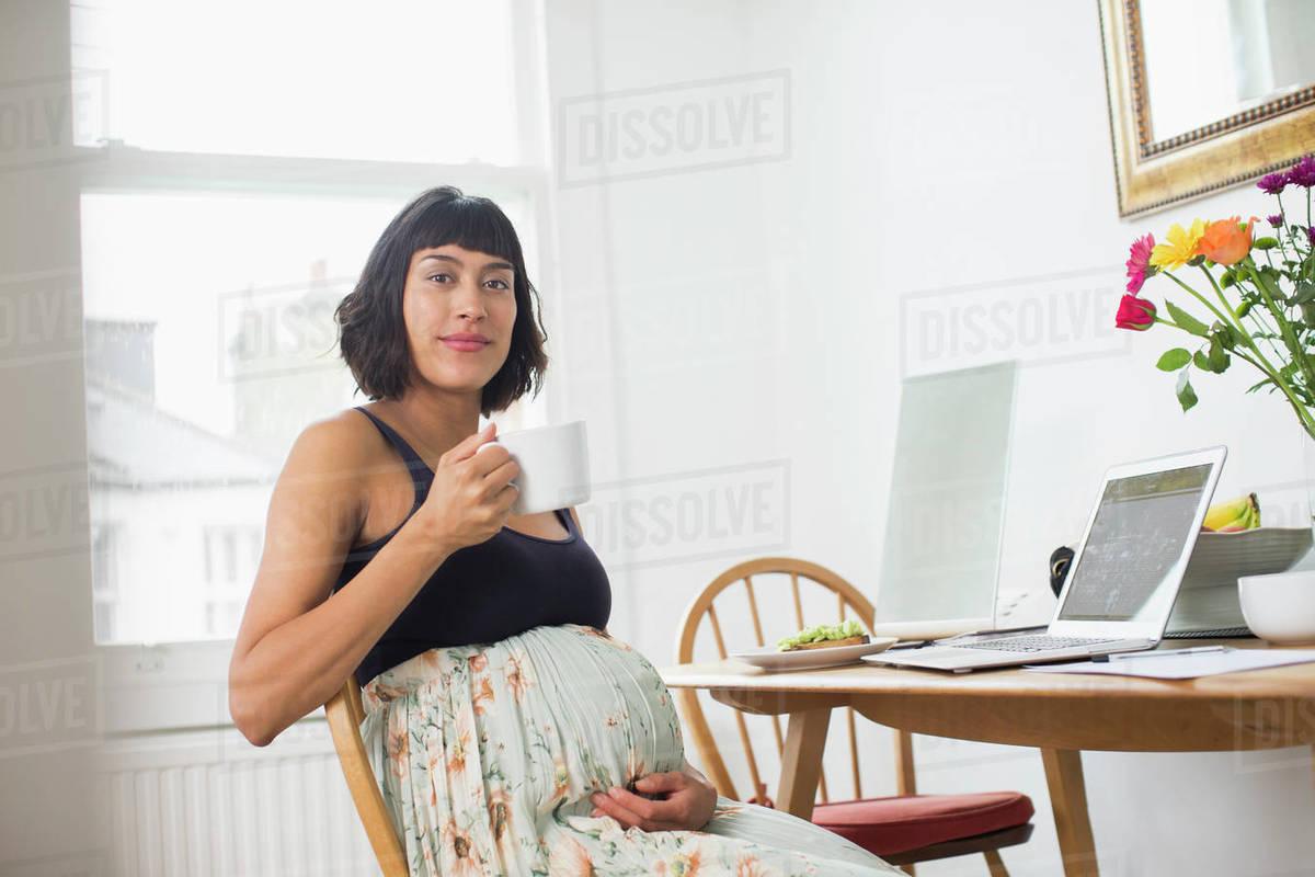 Portrait confident pregnant woman drinking tea at laptop Royalty-free stock photo