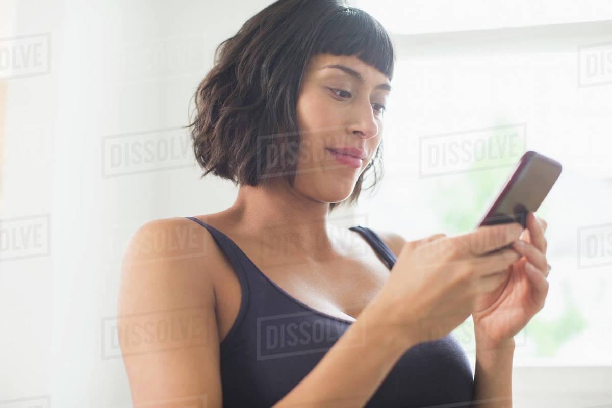 Woman in bra using smart phone Royalty-free stock photo