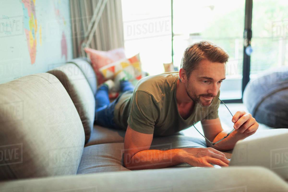 Man relaxing, laying on sofa using laptop Royalty-free stock photo