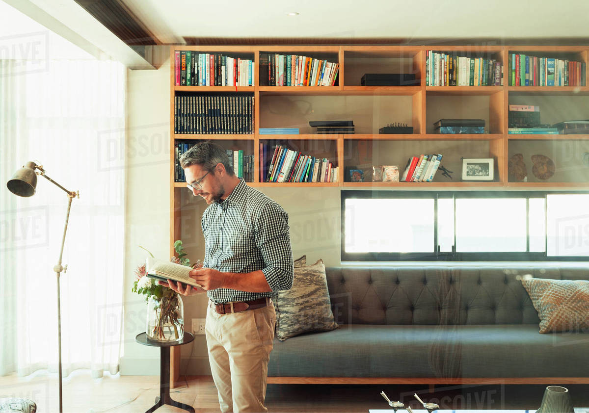 Man reading book in modern living room Royalty-free stock photo