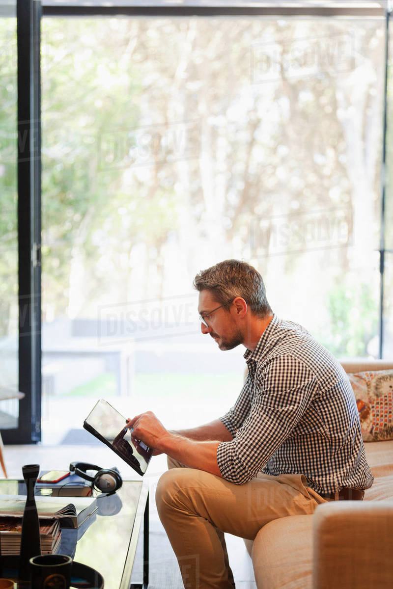 Businessman using digital tablet, working from home on sofa Royalty-free stock photo