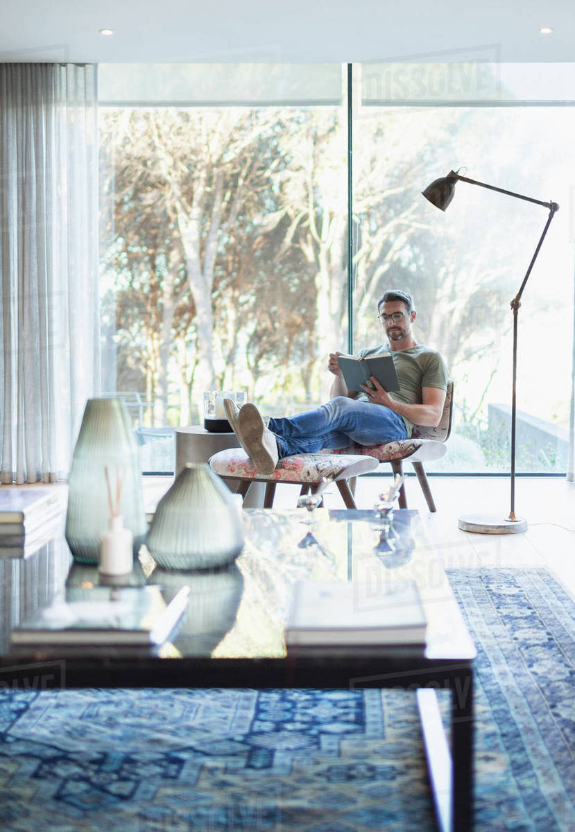Man relaxing with feet up, reading book in living room Royalty-free stock photo