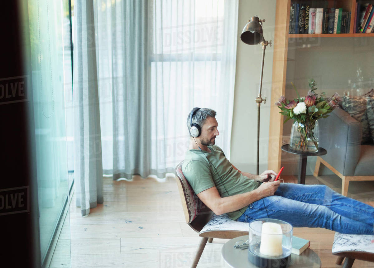 Man relaxing in living room, listening to music with mp3 player and headphones Royalty-free stock photo