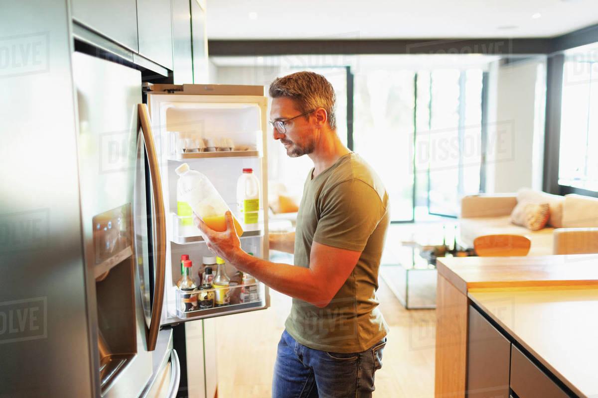 Man holding orange juice at open refrigerator in kitchen Royalty-free stock photo