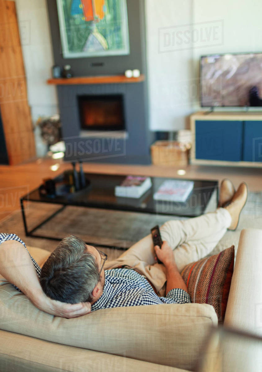 Man relaxing, watching TV on living room sofa Royalty-free stock photo