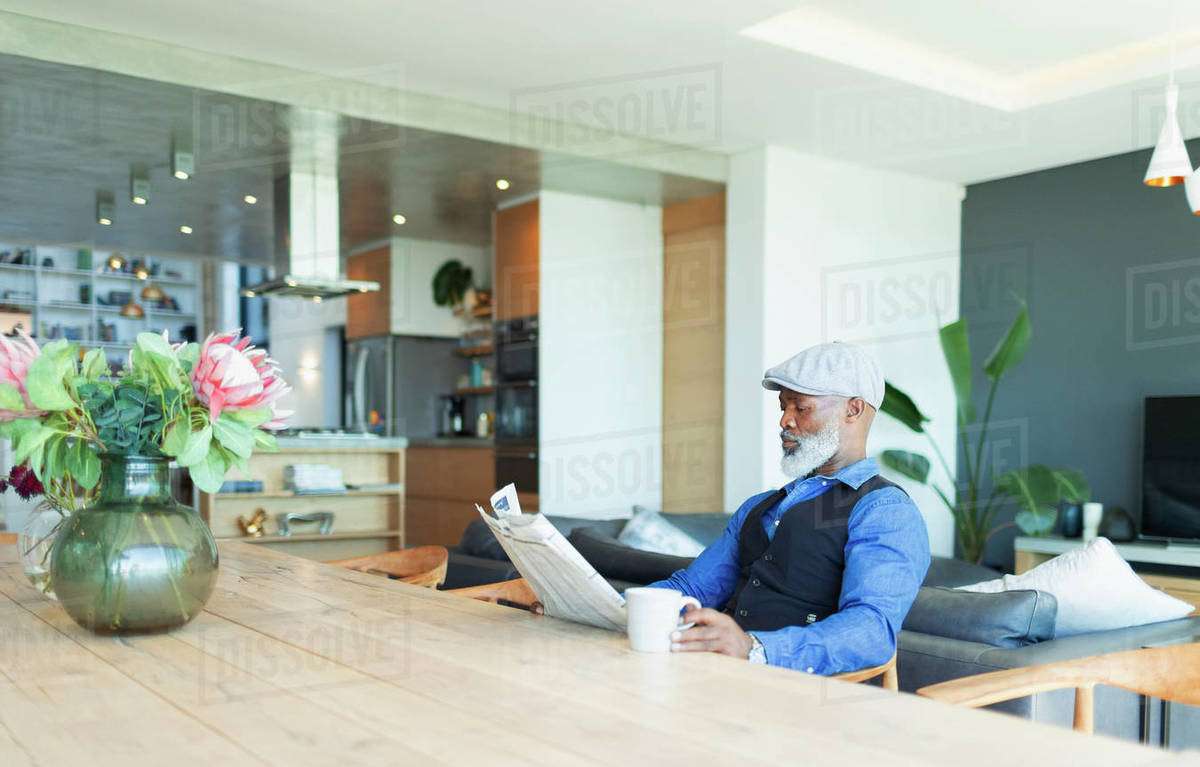 Man reading newspaper and drinking coffee at dining table Royalty-free stock photo
