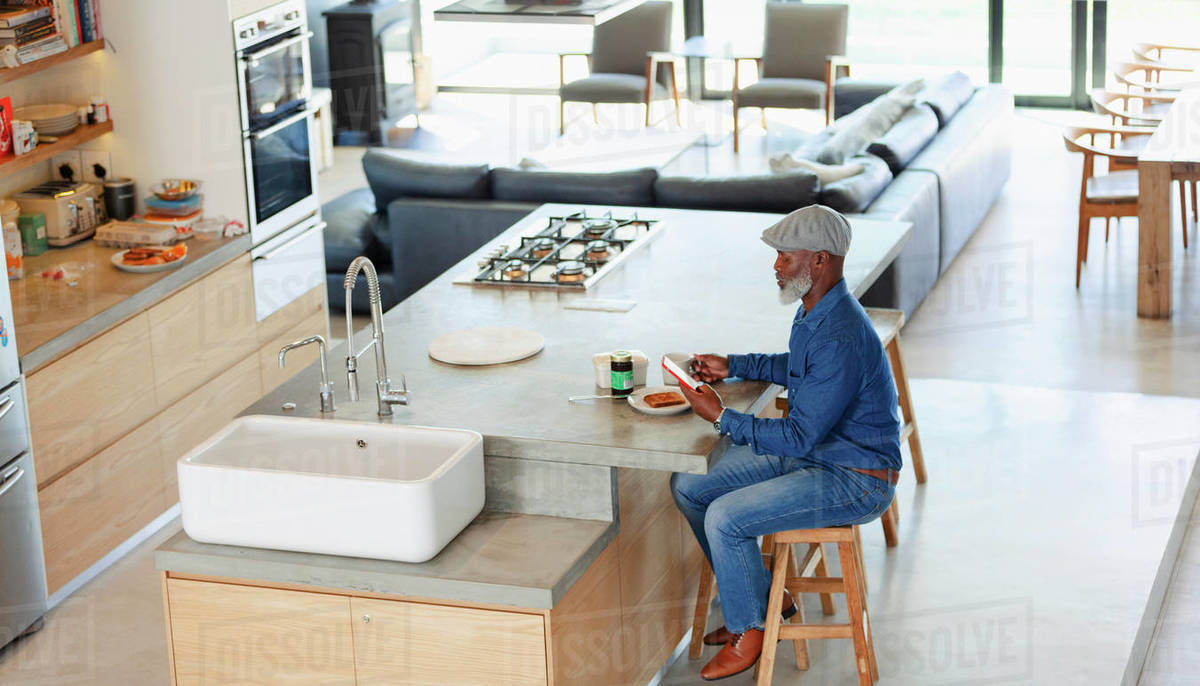 Man eating breakfast and using smart phone in modern kitchen Royalty-free stock photo