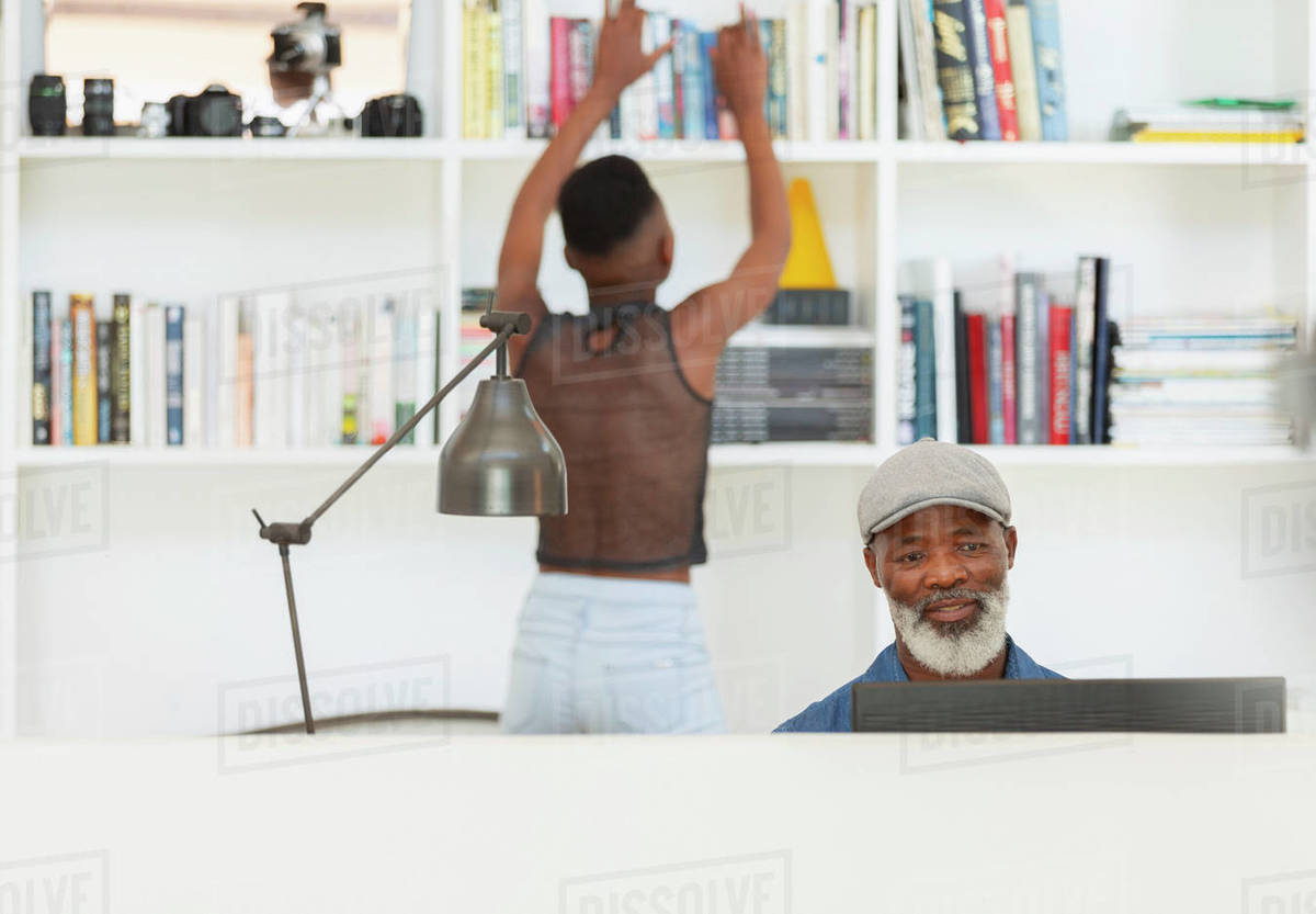 Father using computer and daughter at bookcase in home office Royalty-free stock photo
