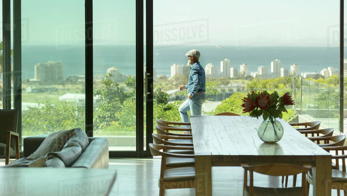 Man standing on sunny patio with scenic view of ocean Royalty-free stock photo