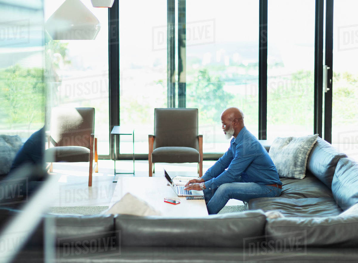 Man using laptop on living room sofa Royalty-free stock photo