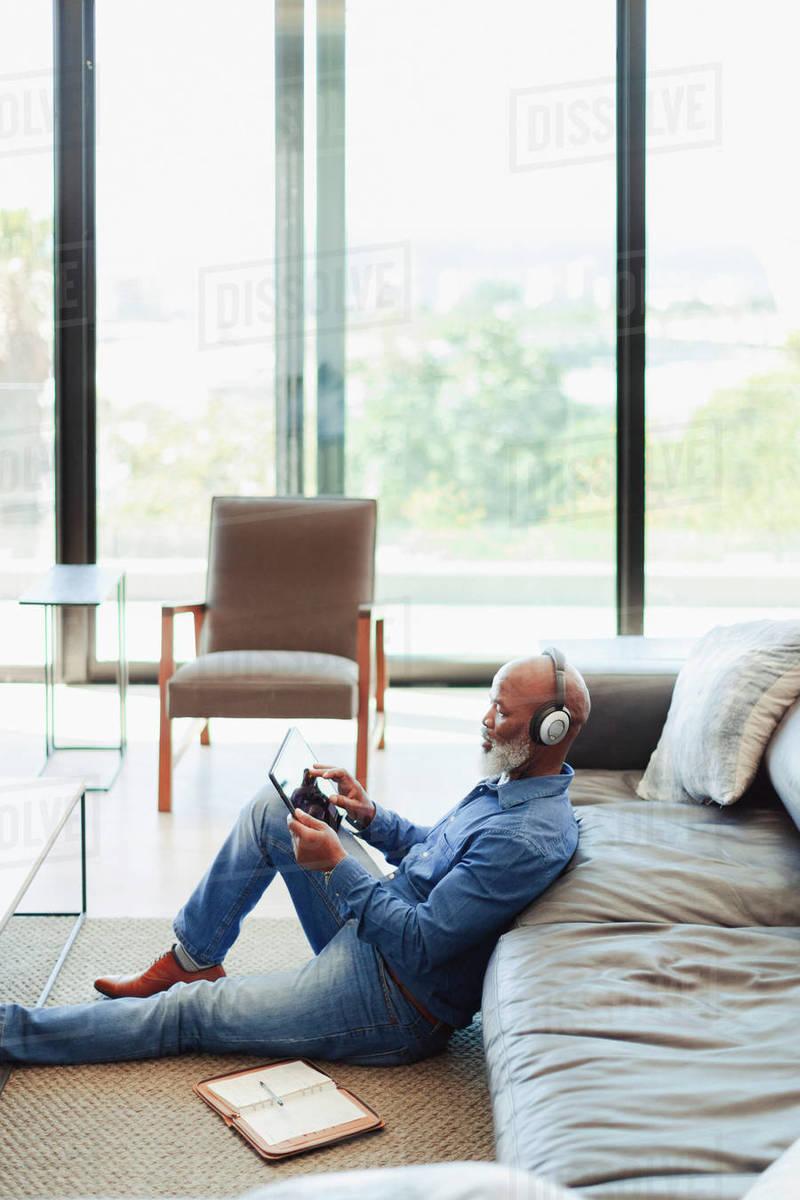 Man with headphones using digital tablet on living room floor Royalty-free stock photo