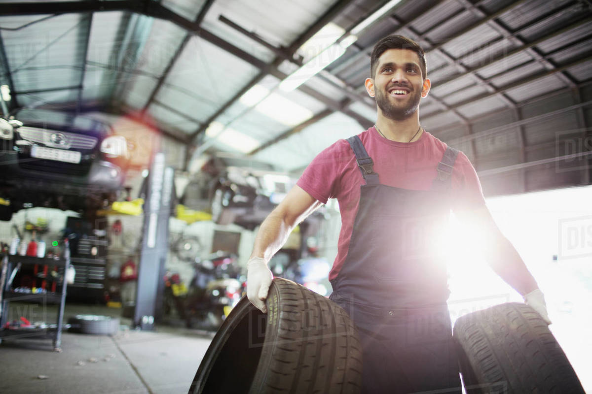 Portrait smiling male mechanic carrying tires in auto repair shop Royalty-free stock photo